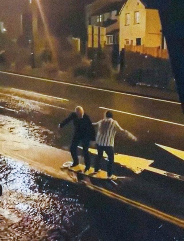 """Stariji par """"surfa"""" na dasci za peglanje prilikom bujice nakon obilnih kiša"""