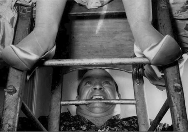 Snagator Butty Sugrue zubima drži stolicu na kojoj sjedi irska pjevačica Birdie Gallagher, 1959.