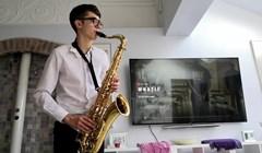 Talentirani mladi muškarac je vježbao sviranje saksofona, a onda ga je nešto smiješno počelo ometati