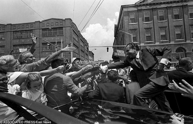 Predsjednik SAD-a Richerd Nixon stoji na braniku auta kako bi se mogao rukovati s ljudima.