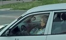Ova starija žena na vratima svog auta ima naljepnice koje bi prolaznike mogle zabrinuti