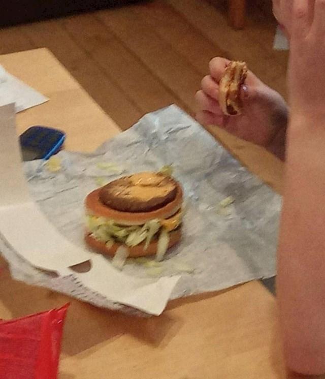 Čovjek koji jede burger sloj po sloj...