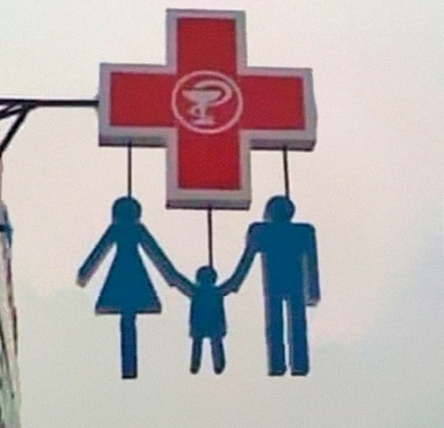 2. Obitelj koja visi sa znaka za ljekarnu.