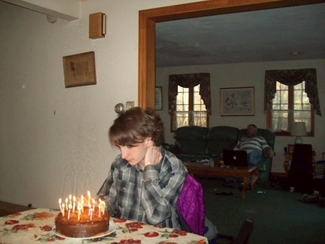 13. Ovaj je otac sjedio na kauču gledajući televiziju, dok sin sjedi sam, spremajući se da puhne svijeće na rođendanskoj torti.
