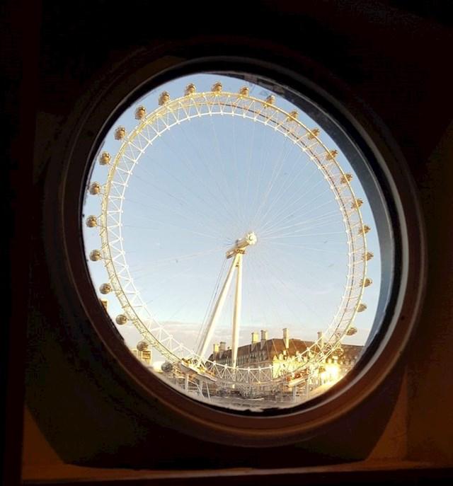 6. Londonsko oko snimljeno kroz prozorčić broda koji plovi Temzom