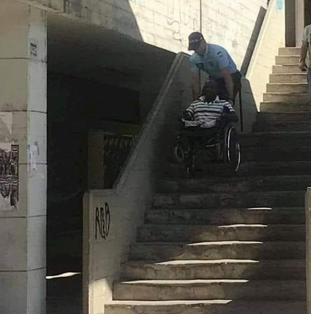 Policajac pomaže invalidu da se spusti niz stepenice.