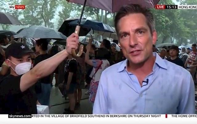 13. Prosvjednik drži svoj kišobran nad novinarom.