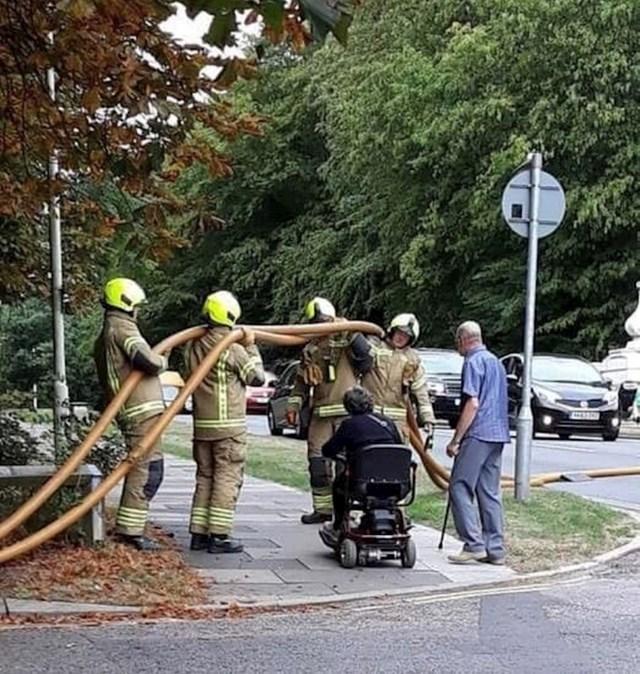 15. Vatrogasci drže crijevo kako bi žena u invalidskih kolicima nesmetano prošla.