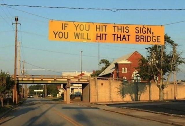 Znak koji upozorava kamione da će, ako njega dotaknu, zapeti za onaj most naprijed
