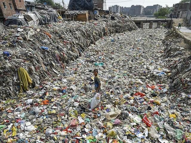 Dječak prikuplja predmete za reciklažu iz presušenog odvoda u Taimoor Nagaru u New Delhiju