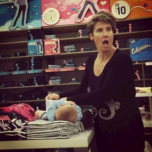 Ova mama presvlači pelenu bebi na odjeći u dućanu