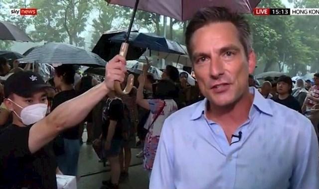 Sudionik protesta pridržava kišobran izvjestitelju