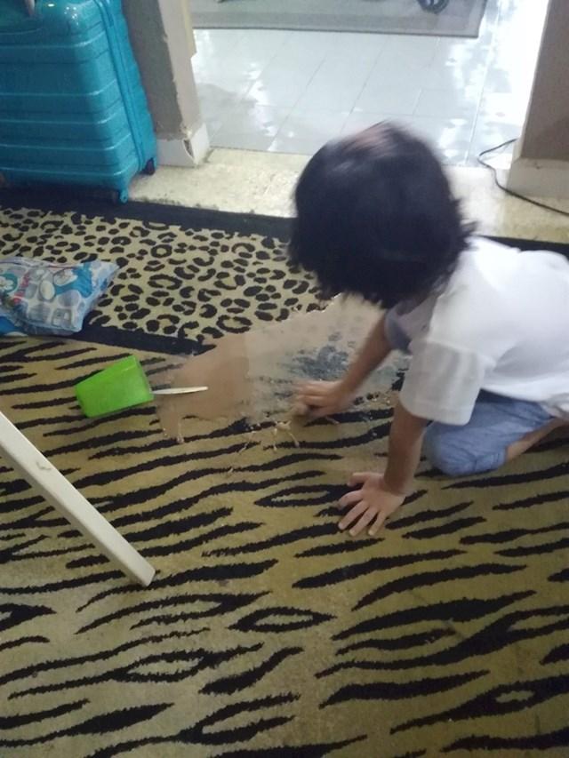 Pokušava počistiti kakao koji je prolila na tepih